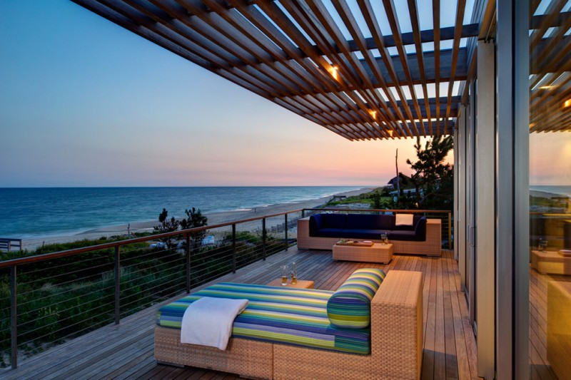 cable railing deck outdoor seating outdoor sofa blue cushion colorfl couch rattan couch white towel coffee table lighting