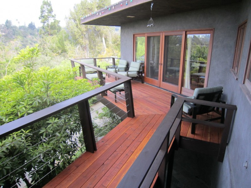 cable railing deck wooden deck floor wooden outdoor armchairs green cushions wood railing cap grey walls glass doors
