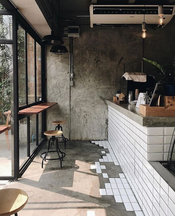 cafe with bare floor but white tiles transition from the bar wall
