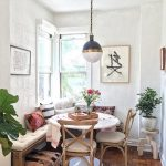 Corner Dining Room With Wooden Bench And Chairs With White Cushions, White Wall, Ball Pendant, Wood Flooring, Ottoman, Pillows, Plants, Flowers On The Table