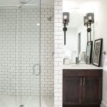 Craftsman Style Wall Sconce Dark Wooden Vanity White Subway Wall Tile White Mosaic Floor Tile Artwork Sink Wall Mirror Shower Head Undermount Sink Faucet