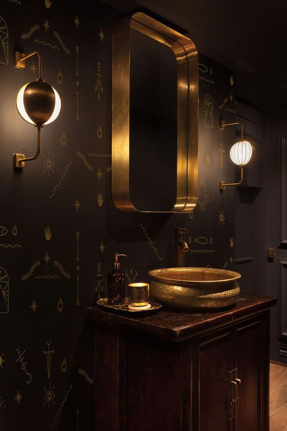 dark walls with golden egyptian images, golden sink, golden framed mirror, brown wooden cabinet