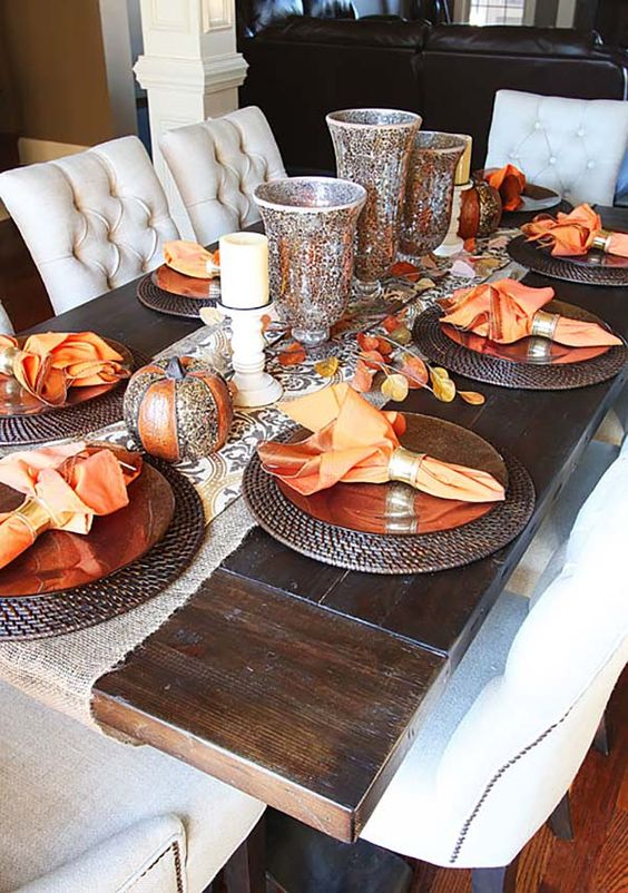 dining table with wooden table, white cushioned chairs, bronze plate with orange cloth, silver ornaments
