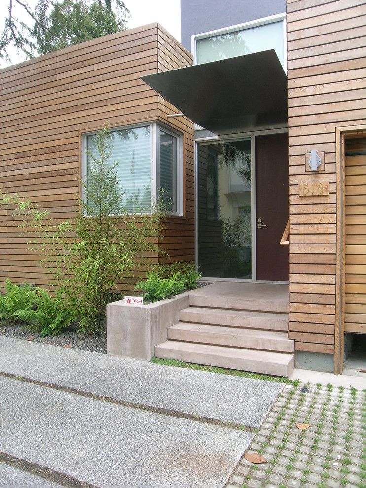 entry door with one sidelight corner glass windows concrete grass outdoor plants wooden walls entry stairs wall sconce