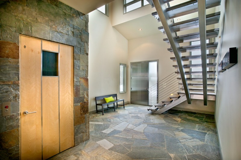 entry door with one sidelight stainless steel door frosted glass doors staircase stone walls stone floor black bench window
