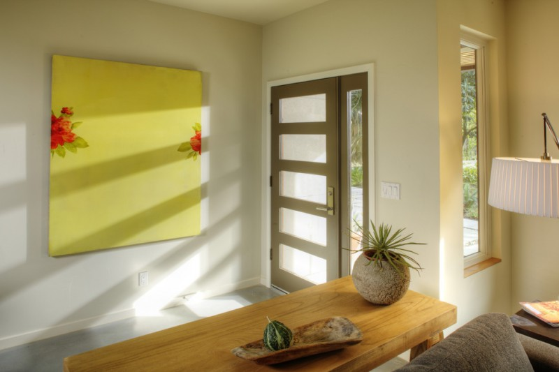entry door with one sidelight yellow artwork wooden entrywat table floor lamp grey sofa glass window grey floor