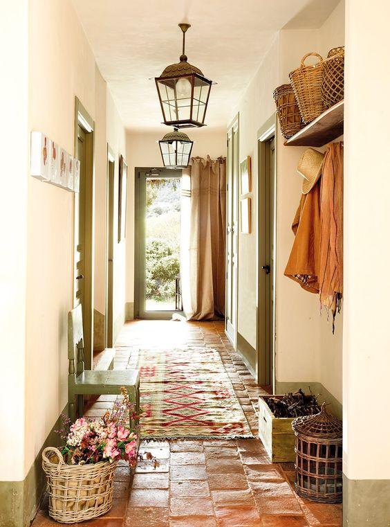 hallway with terracotta tiles, chair, morocco pendant, colourful rug, basket