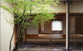 japanese house with a patch of soil inside the house separated by glass window and traditional sliding dooor, with grass, stones, and a tree