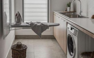 kitchen with grey floor, brown cabinet, white marble top, sink, washing machine under, rattan baskets, ironing table near