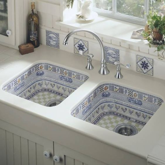 kitchen with white marble sink, blue chicken pattern inside sinks, metal faucet