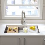 Kitchen With White Marble Top, White Wooden Cabinet, Stainless Steel Sink Features Three Graduated Ledges In The Basin