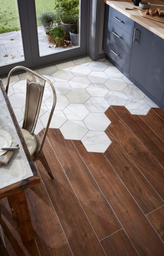 kitchen with wooden floor combined with white hexagonal tiles near the door