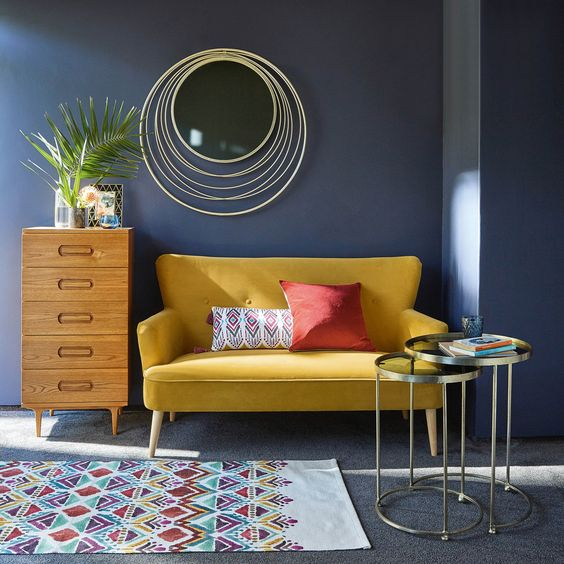 living room with blue wall, metal coffee table iwth glass top, wooden cupboard, decoration, yellow sofa