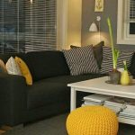 Living Room With Dark Grey Sofa And Rug, White Coffee Table, Plants, Yellow Woven Ottoman
