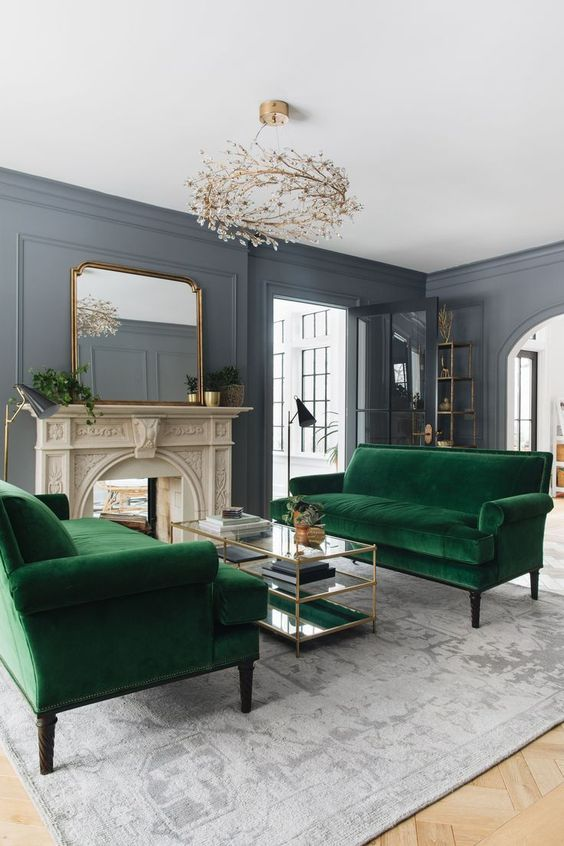 living room with grey rug, green sofa, white stone fireplace, coffee table with glass top, mirror, swirling chandelier