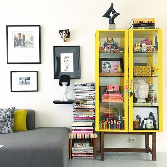 living room with grey rug, grey sofa, side table, yellow shelves on top of the table