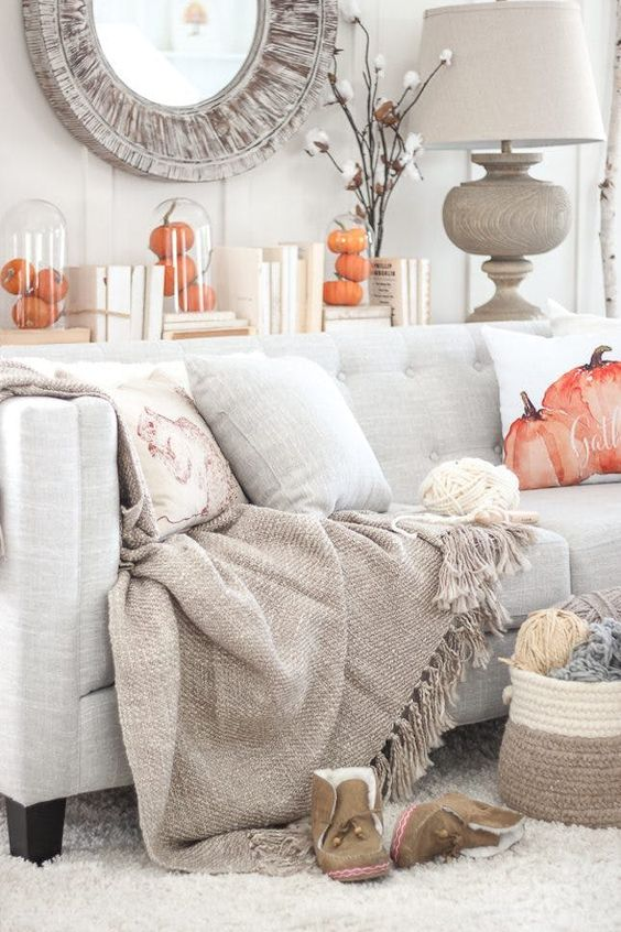 living room with light grey rug and sofa, pumpkin pillow, pumpkin decorations, mirror