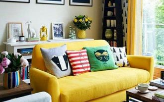 living room with striped rug, grey chair, yellow sofa, yellow curtain, shite shelves, paintings, colorful pillow