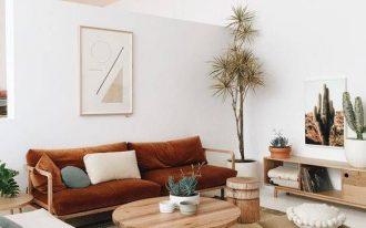living room with terracotta brown sofa, white chair, floor pillows, coffee table, wooden stool, plants, cabinet