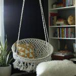 Living Room With Warm Rug, Whte Bookshelves, White Fur Ottoman, White Macrame Round Swing