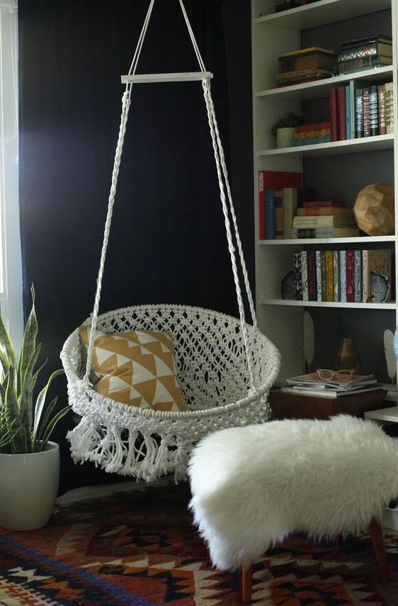 living room with warm rug, whte bookshelves, white fur ottoman, white macrame round swing