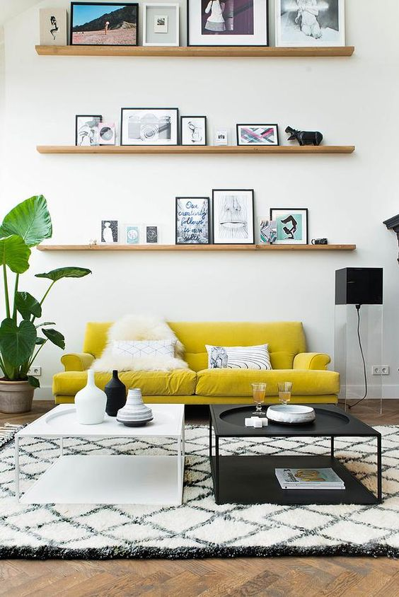 living room with white rug, white and black coffee table, black floor lamp, plants, shelves, yellow sofa
