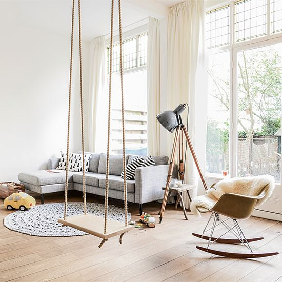 living room with wooden floor, grey L sofa, white wall, midcentury modern rocking chair, macrame rug, floor lamp, wooden swing