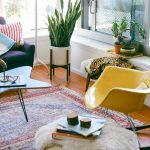 Living Room With Wooden Floor, Wide Glass Windows, Rug, Dark Purple Sofa, Yellow Rocking Chair, Plants, White Lamps, Light Brown Ottoman