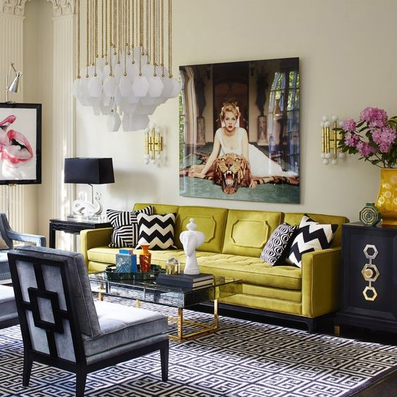 living room with yellow sofa, grey sofa, black and white rug, white wall, black cabinet, black table lamp, flowers, scoces, beautiful white chandelier