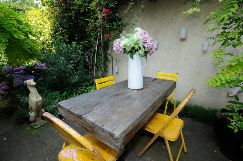 metal patio dining chairs yellow metal chairs white flowers jug wall decorations garden statue wooden outdoor dining table black floor tile
