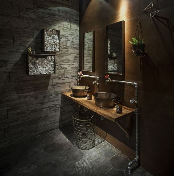neat bathroom with honeyed brown wall, bronze sink, wire basket, mirrors