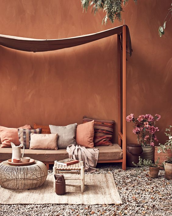patio with terracotta wall, orange wooden bench with drapery, brown cushions and pillows, brown rug, rattan coffee table