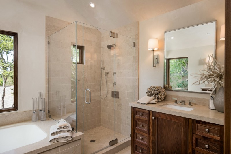 polished nickel mirror glass shower doors shower head wooden vanity sink faucet wall sconces built in bathtub windws beige tiles countertop