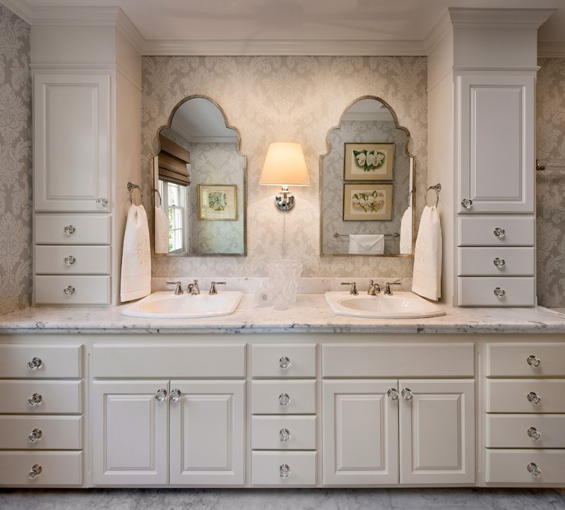 polished nickel mirror wall sconce towel rings white vanity drawers white granite countertop floral wallpaper white sinks faucet grey floor tile