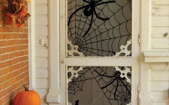 porch with big spider accessories on the white door glass, orange pumpkins, bench,