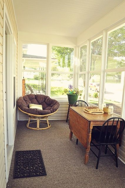small sunroom with grey rug, white wooden wall, large windows, rattan globe chair with grey cushion, wooden table with two black chairs