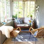 Small Sunroom With Wooden Floor, Brown Rug, Striped Rug, Rattan Chairs, Wooden Sofa, Grey Walls, Plants, Rattan Lamp