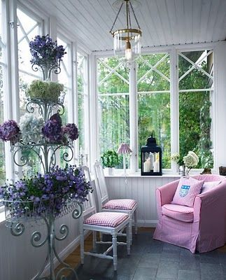 sun room with pink chair, white chairs with pink cushioin, grey tiles, lavender flowers, clear glass lamp