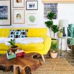 Warm Living Room With Yellow Sofa, Rattan Rug, Wooden Coffee Table, White Walls, Tile Floor, Plants