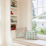 White Bench Near The Window With Storage Under, Nude Cushion And Blue Pillows, Shelves On The Back