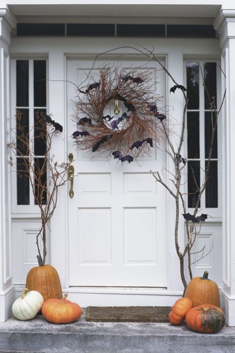 white wooden door with black bats, pumpkins, dried branches