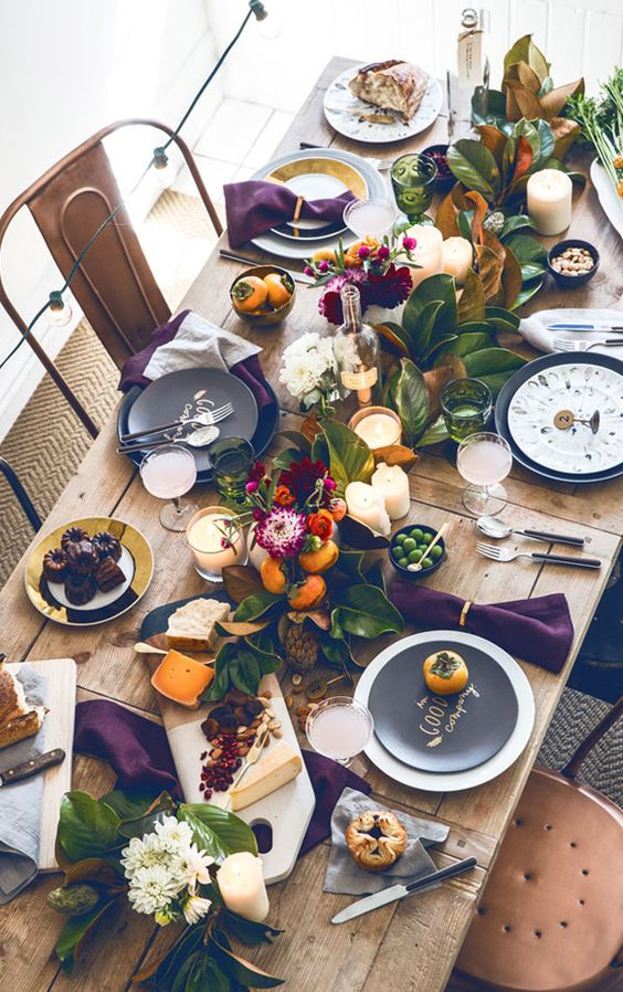 wooden dining table with purple cloth, white and black plates, flowers and plants centerpiece