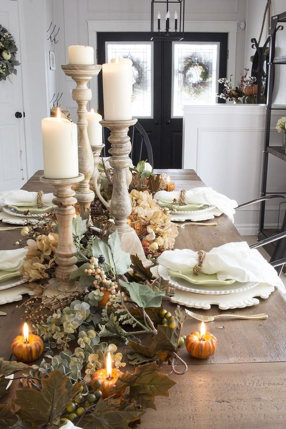 wooden dining table with white plate set, candles, plants, pumpkins accessories