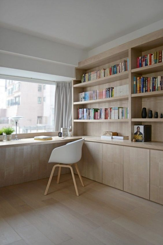 a room with large windows with bookshelves, table infront of windows, white midcentury chair