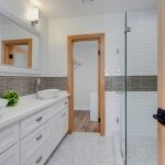 Frameless Shower Door Sweep Grey Subway Tile White Wall Tile Marble Flooring Wooden Doors White Vanity White Sink Bowl Wall Mirror Wall Sconces