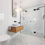 Frameless Shower Door Sweep Wall Mounted Head Shower White Walls Tiles Herringbone Floor Tile Pendant Lamp Wall Mirror Wall Mounted Wooden Cabinet White Sink Wall Moun