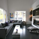 Gray Table Glass Windows Floor Cushions Modern Fireplace Built In Shelves Black Floor Tile Grey Sectional Sofa Grey And Purple Pillows Colorful Artwork