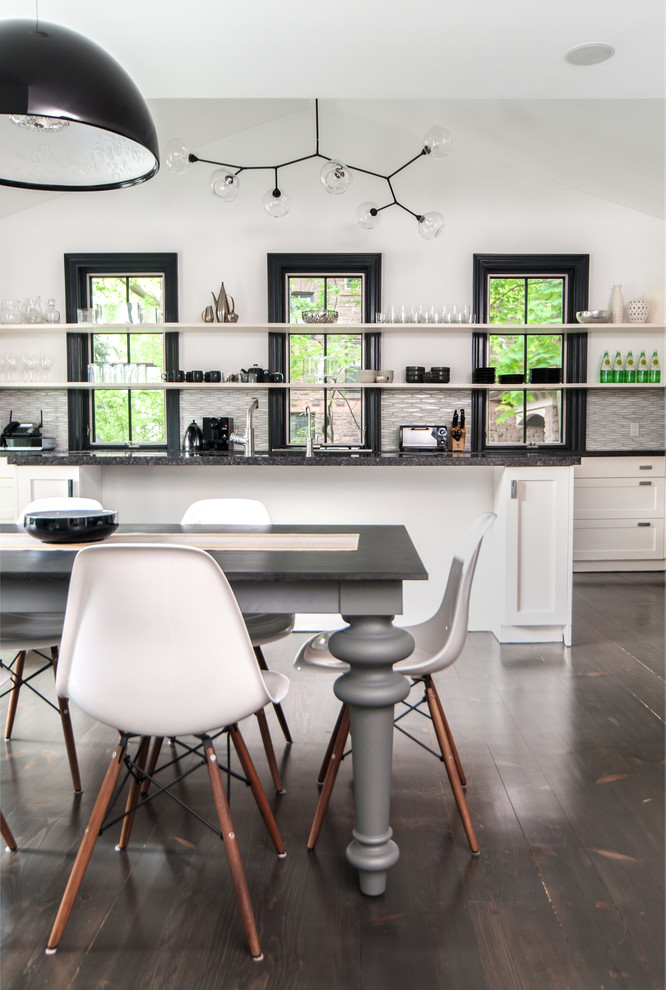 gray table wooden floor white dining chairs black framed glass windows white cabinets chandelier black granite countertops white island white shelves