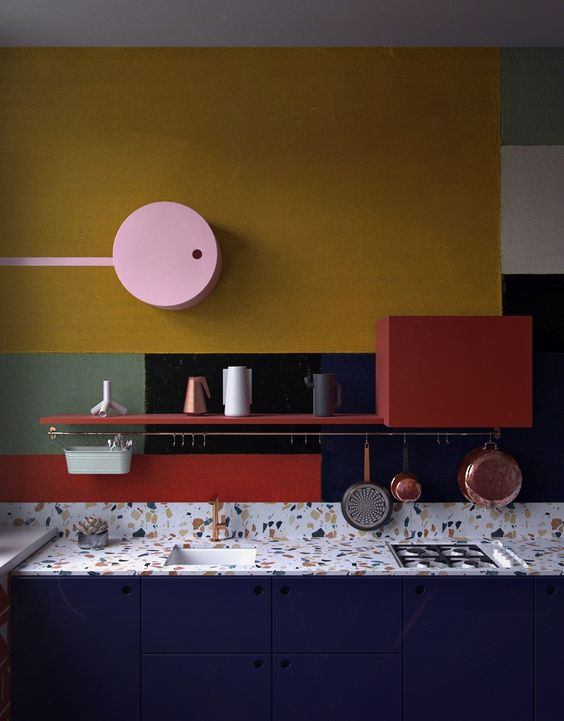 kitchen with yellow, black, grey, blue, red color blocks on the wall, white with coor bits patter counter top, blue cabinet, red shelves