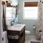 Light Blue Wall Painted Small Bathroom With White Toilet, White Framed Mirror, White Framed Window, Brown Wooden Shelves With White Top